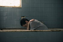 Mohamad Itani Young woman sitting in bath in abandoned house