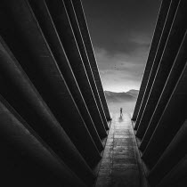 Zoltan Toth SILHOUETTED MAN BY TALL FUTURISTIC BUILDINGS Men