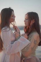 Inna Mosina TWO WOMEN TOUCHING ON BEACH AT SUNSET Women
