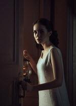 Ekaterina Pavlova BRUNETTE WOMAN OPENING DOOR HOLDING LAMP Women