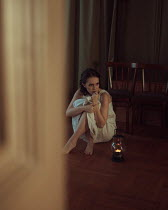 Ekaterina Pavlova BRUNETTE WOMAN SITTING ON FLOOR WITH OIL LAMP Women