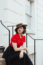 Matilda Delves WOMAN IN HAT SITTING ON STEPS OUTSIDE HOUSE Women