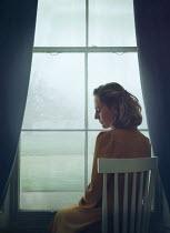 Mark Owen SAD BLONDE WOMAN SITTING INDOORS BY WINDOW Women