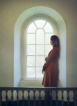 Mark Owen DAYDREAMING BLONDE WOMAN STANDING INDOORS BY WINDOW Women
