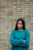 Shelley Richmond ASIAN TEENAGE GIRL STANDING BY WALL OUTDOORS Women