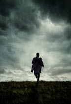Silas Manhood MAN IN RAINCOAT RUNNING IN STORMY COUNTRYSIDE Men