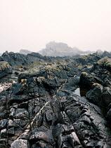 David Baker Rock formation under fog