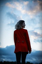 Natasza Fiedotjew Blonde woman in red coat at sunset