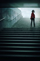 Natasza Fiedotjew Woman in red coat with gun on underground stairs