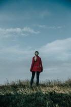Natasza Fiedotjew Blonde woman in red coat standing in field Women
