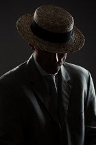 Magdalena Russocka man wearing suit and boater hat sitting inside