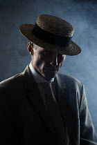 Magdalena Russocka man wearing suit and boater hat sitting in smoky room