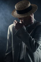 Magdalena Russocka man wearing suit and boater hat holding cigarette inside