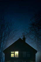 Lee Avison person in silhouette in window of house at night