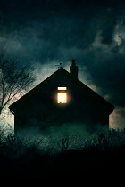 Lee Avison house at night with window light
