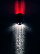 Magdalena Russocka car with hedalights and rear lights on snow from above at night