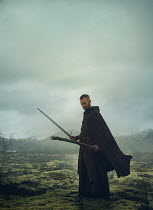 Mark Owen MAN IN CAPE HOLDING STAFF AND SWORD IN BLEAK LANDSCAPE Women