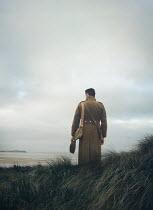 Mark Owen SOLDIER STANDING IN DUNES WATCHING SEA