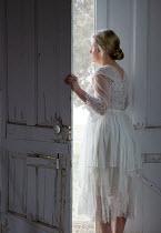 Rodney Harvey WOMAN IN WHITE OPENING OLD WOODEN DOOR