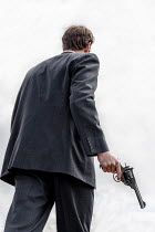 CollaborationJS MAN IN SUIT CARRYING GUN OUTDOORS