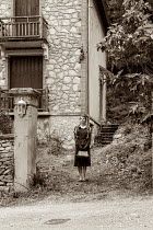 Elly De Vries RETRO WOMAN STANDING OUTSIDE HOUSE