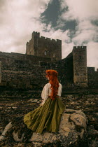 Rebecca Stice WOMAN WITH RED HAIR ON ROCK BY CASTLE