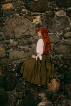 Rebecca Stice WOMAN WITH LONG RED HAIR SITTING BY STONE WALL