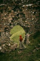 Rebecca Stice MEDIEVAL WOMAN WITH RED HAIR STANDING BY CASTLE WALL