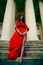 Marina Chebanova WOMAN IN RED DRESS OUTSIDE BUILDING WITH PILLARS