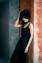 Marina Chebanova WOMAN IN TOP HAT LEANING BY WEATHERED BUILDING