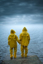 Magdalena Russocka man and woman wearing yellow rainsuits holding hands standing on deck by lake