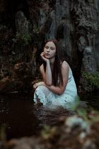 Greta Larosa YOUNG GIRL SITTING IN POOL BY ROCK