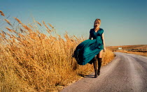 Metin Demiralay WOMAN IN GOWN AND BOOTS WALKING ON COUNTRY ROAD