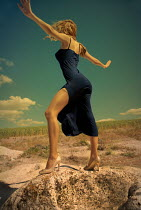 Metin Demiralay WOMAN IN HIGH HEELS ON ROCK IN COUNTRYSIDE