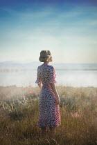 Ildiko Neer Blonde woman standing by lake