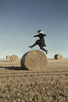 Laurence Winram WOMAN JUMPING OVER HAYSTACK