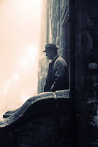 Laurence Winram Man in hat and coat by stone wall