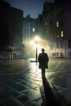 Laurence Winram Man in hat and coat walking in public square at night