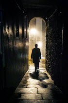 Laurence Winram Man in hat and coat walking in tunnel at night