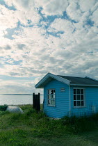 Carmen Spitznagel SMALL BLUE HUT WITH BOAT BY WATER