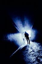 Tim Robinson SILHOUETTED MAN WALKING IN CONCRETE PASSAGEWAY