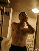 Maria Yakimova TATTOOED MAN WITH WET T-SHIRT COVERING FACE INDOORS