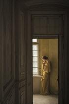 Dorota Gorecka DAYDREAMING GIRL STANDING IN SHABBY INTERIOR