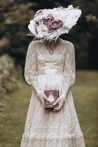 Magdalena Russocka historical woman wearing hat holding book standing in garden