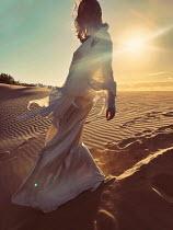 Elena Tyagunova WOMAN IN WHITE SILK DRESS ON SUNLIT BEACH