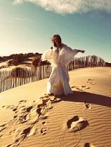 Elena Tyagunova WOMAN IN WHITE GOWN ON SAND DUNES
